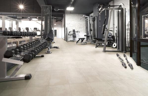 Ein Fitnessstudio mit Fliesen von Margres Tool in der Farbe White für ein offenes Flair.