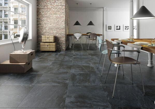 Die Serie Keraben Nature in der Farbe black in einem großen Wohn-/Essbereich auf dem Boden verlegt.