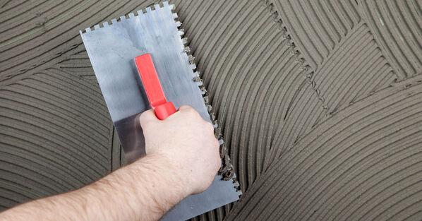 Flexkleber wird mit einer gezahnten Kelle aufgetragen und verstrichen.