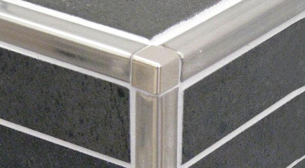 Eine verflieste Ecke mit Edelstahl Schienen in eckigem Design.