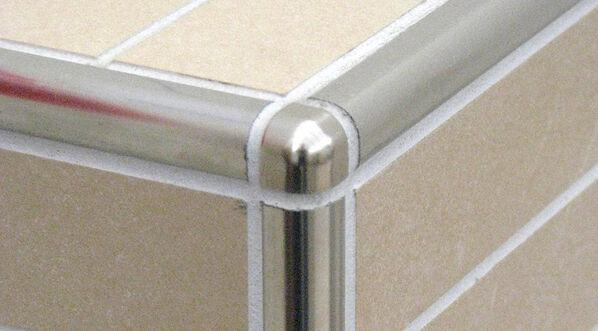 Eine verflieste Ecke mit Edestahlschienen in einem runden Design.