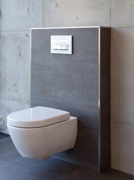 Gestaltungstipp für das Bad: Eine weiße Toilette vor einem dunklen Vorwandelement, das mit anthrazitfarbenen Fliesen verlegt wurde - dieselben Fliesen sind auch auf dem Boden verlegt.
